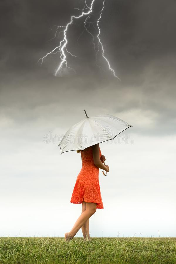 Girl with umbrella in storm stock photography