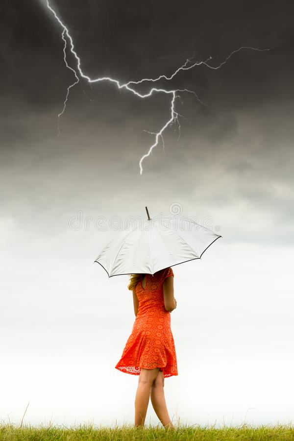 Girl with umbrella in storm stock photo
