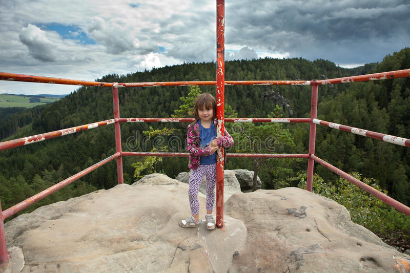 Girl standing on top of rock. Girl standing on top of large rock, with safety railing, smiling and holding a vertical post royalty free stock photo