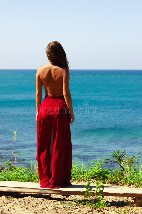 Girl standing topless in red skirt above the sea looking royalty free stock image