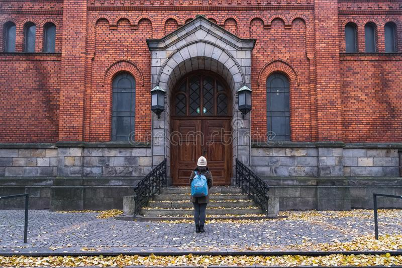 A girl standing toward a red brick building in autumn, in the center of Malmo, Sweden royalty free stock photos