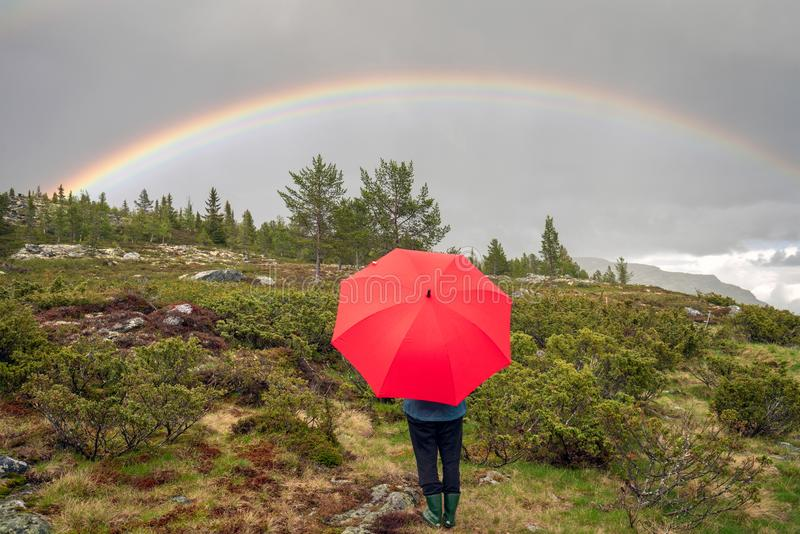 A girl standing under a beautiful rainbow and dark skies with a red umbrella in the middle of a green natural landscape scenery wi stock photography