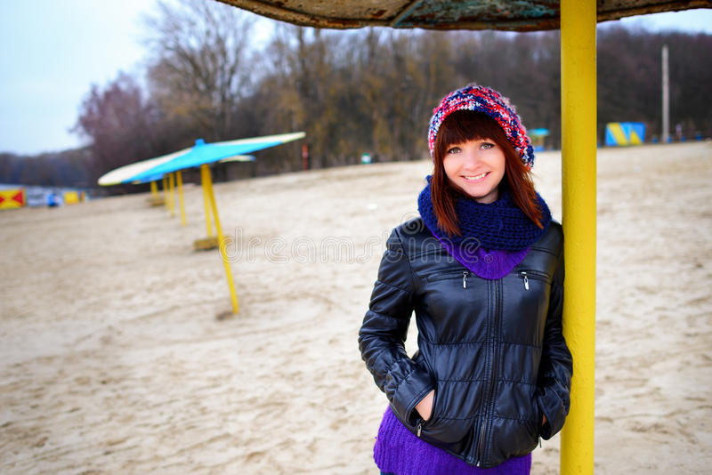 Girl standing under an umbrella on the beach in autumn royalty free stock photography