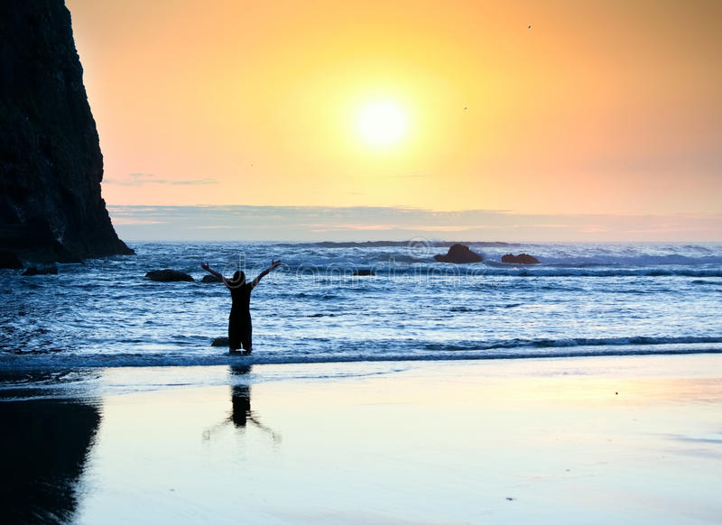 Girl standing in waves, arms raised to sky at sunset stock photo
