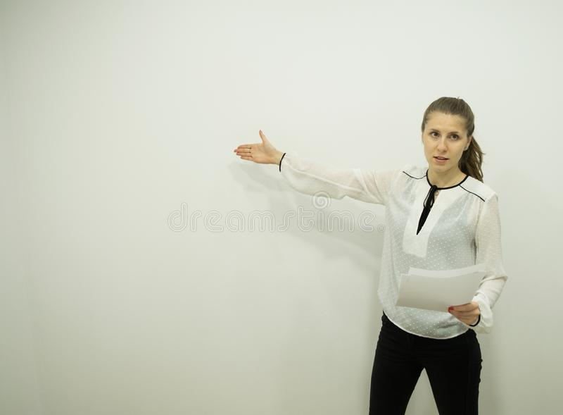Girl is standing by the white wall and speaking in one hand holds a report, the other hand indicates where to look royalty free stock photography