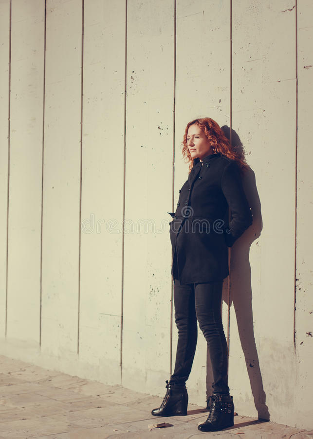 Girl stands against a wall. Girl with red hair stands leaning against a wall background stock images