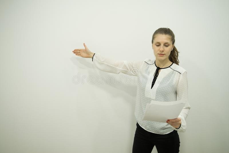 girl stands against a white wall and reads a report, having lowered her eyes into it, holds sheets in one hand, indicates with th royalty free stock image