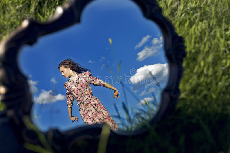 Girl Stands On Background Sky Reflected In Mirror Stock Images