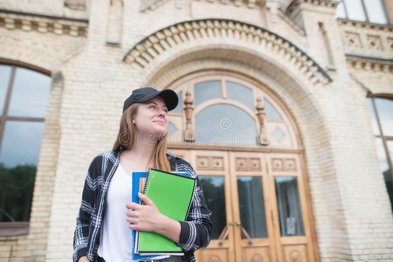 Girl stands at the entrance to college with notebooks in her hands. Portrait of an attractive student girl royalty free stock photography