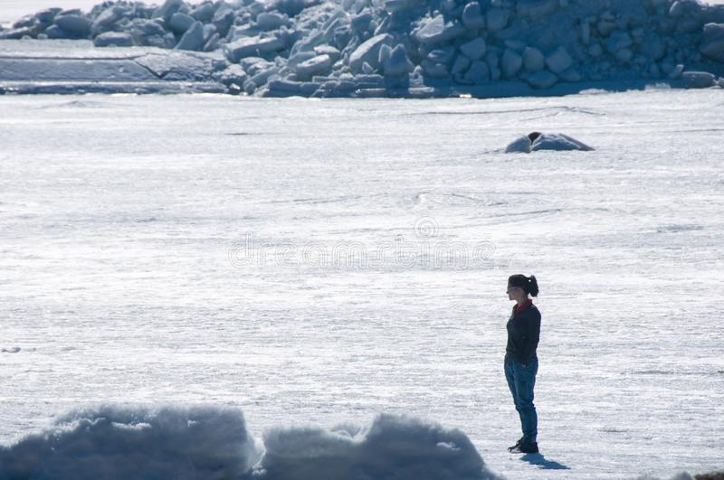 Girl stands on frozen sea and looks around royalty free stock images