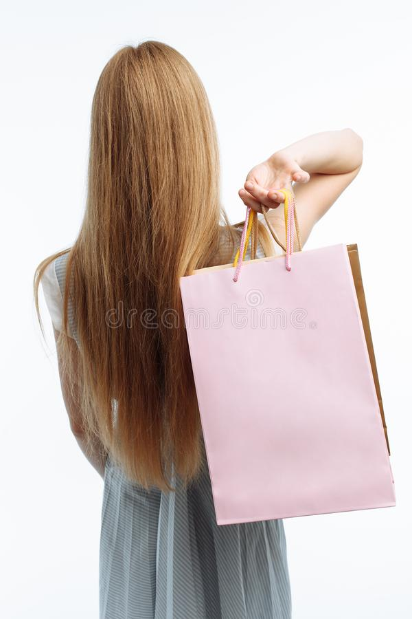 the girl stands with her back, with gift bags, and shows purchases in front of the camera, on a white background, suitable for ad stock images