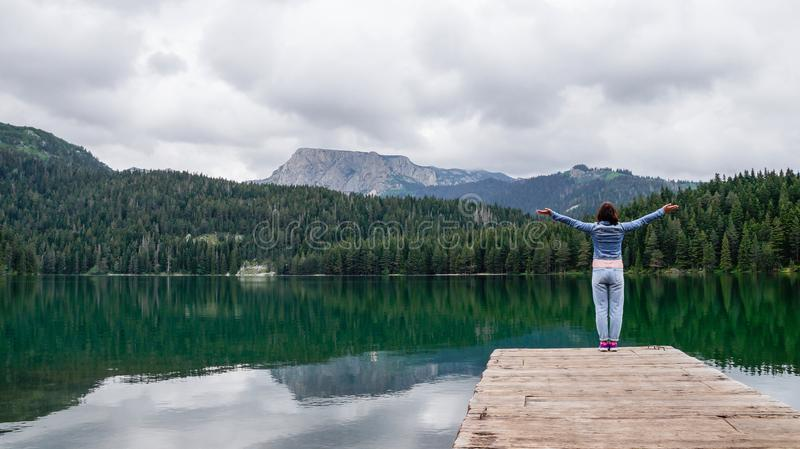 The girl stands with her hands up on the pier of black lake in the national Park Durmitor. Montenegro. stock photography