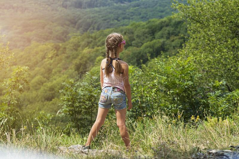 Little girl looks at the mountains from high.A girl stands a hill on a summer sunny day. A girl stands a hill on a summer sunny day.Little girl looks at the stock image