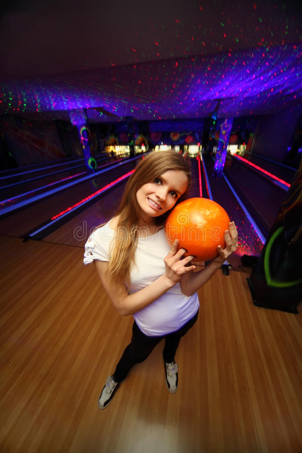 Download Girl Stands And Hugs Ball In Bowling Club Stock Photos - Image: 22736093