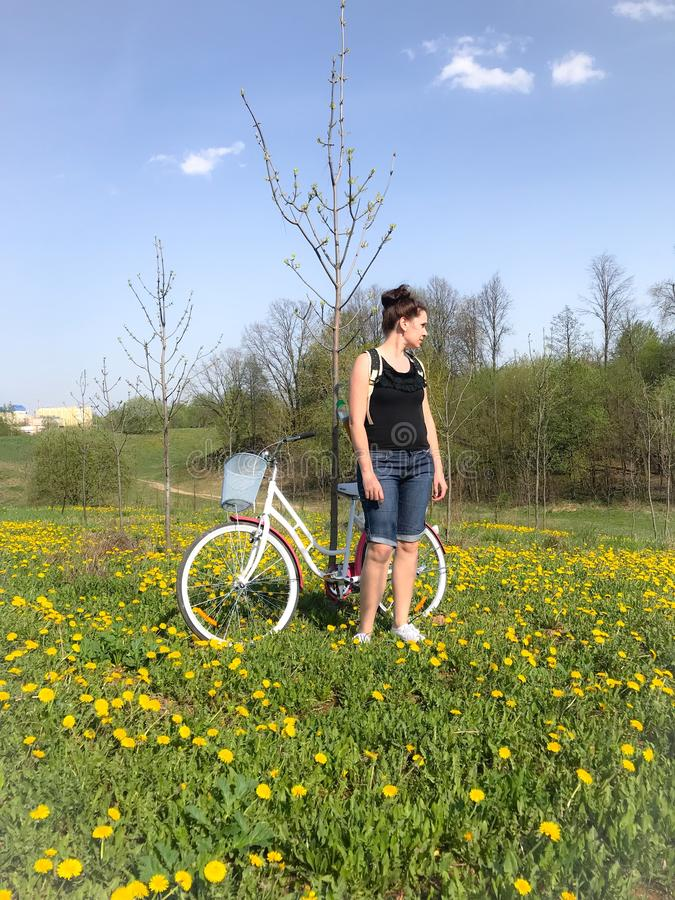 A girl stands next to a bicycle in the spring meadow. Behind her backpack. There are many flowering dandelions in the meadow stock image
