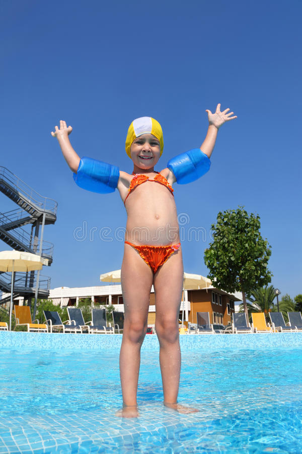 Free Girl Stands On Skirting In Pool Near Hotel Stock Photography - 18360642