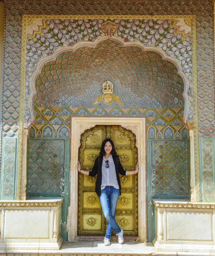 Girl stands before Rose Gate in City Palace, Jaipur, India. Single young Chinese girl stands before Rose Gate - Winter Gate , located in the City Palace, Jaipur royalty free stock images
