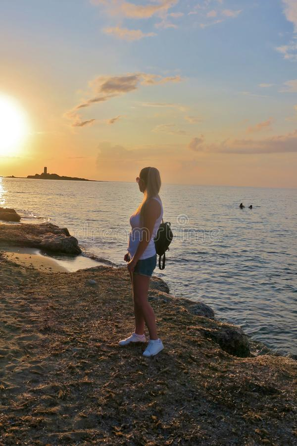 Girl stands on the seashore and looks at the beautiful sunset royalty free stock images