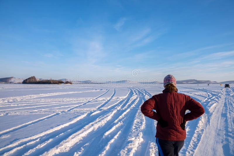 Girl stands on a snow-white frozen lake and looks at the tracks of cars running away into the distance to the horizon on a stock photo