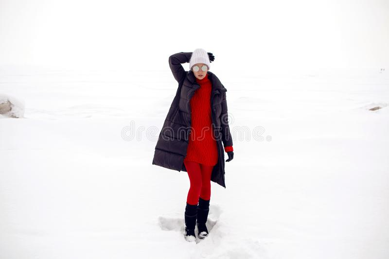 Girl stands in a snowy field in a jacket stock photography