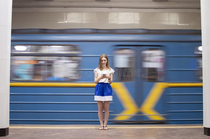 Girl stands on a subway platform and listens to music on the background of a passing train, a student uses a phone in the subway, royalty free stock images