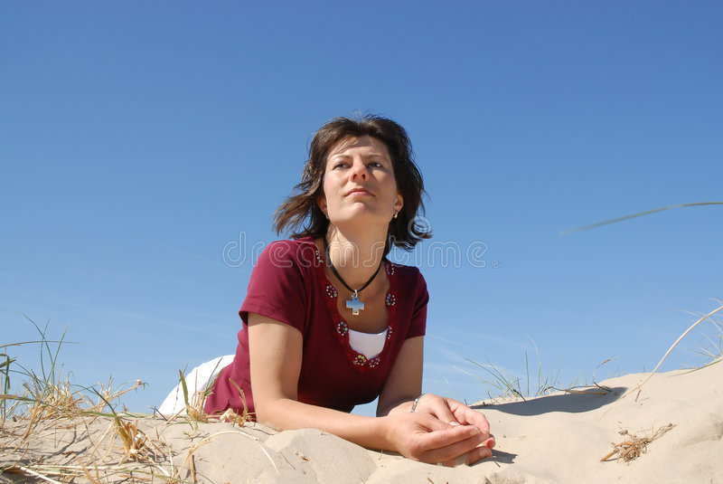Girl staring. In the distance while lying on the beach royalty free stock photography