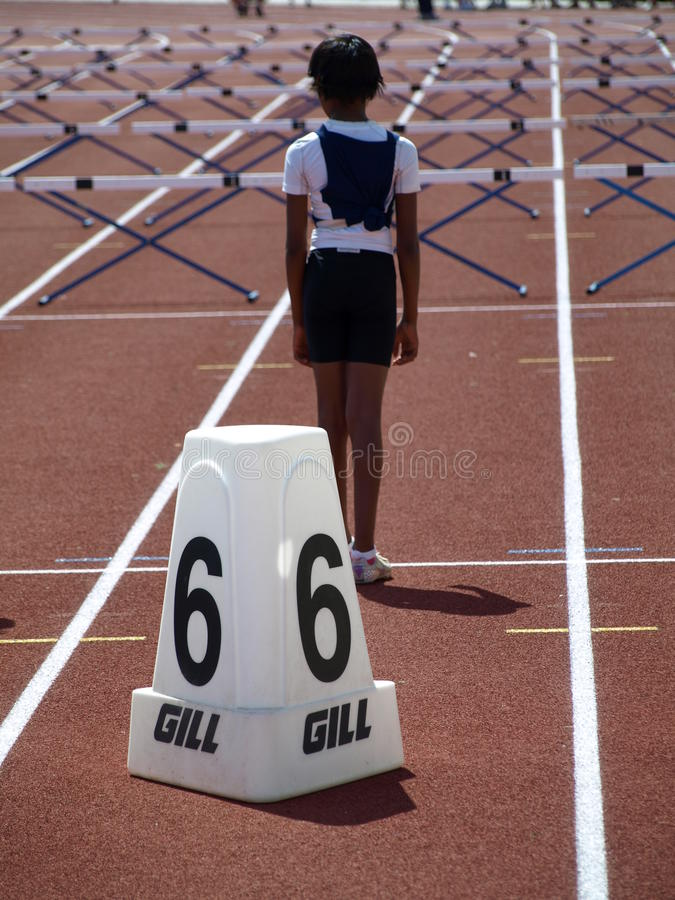 Girl on the start. Girl stands at the start of the hurdles distance on line number six on the BC Junior Development Track and Field Championships July 23, 2011 stock photography