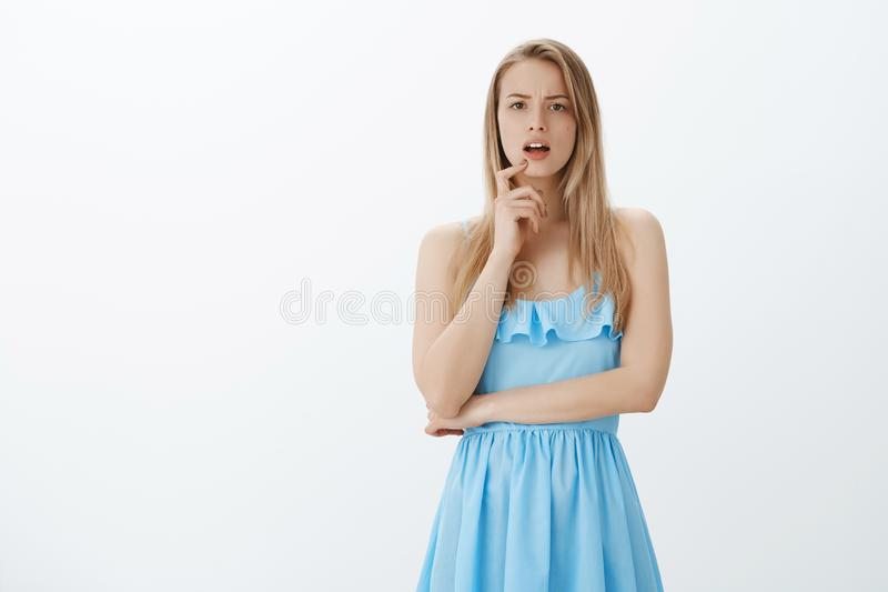 Girl starting realize what happening having idea, standing with opened mouth as frowning and touching lip with finger royalty free stock photo