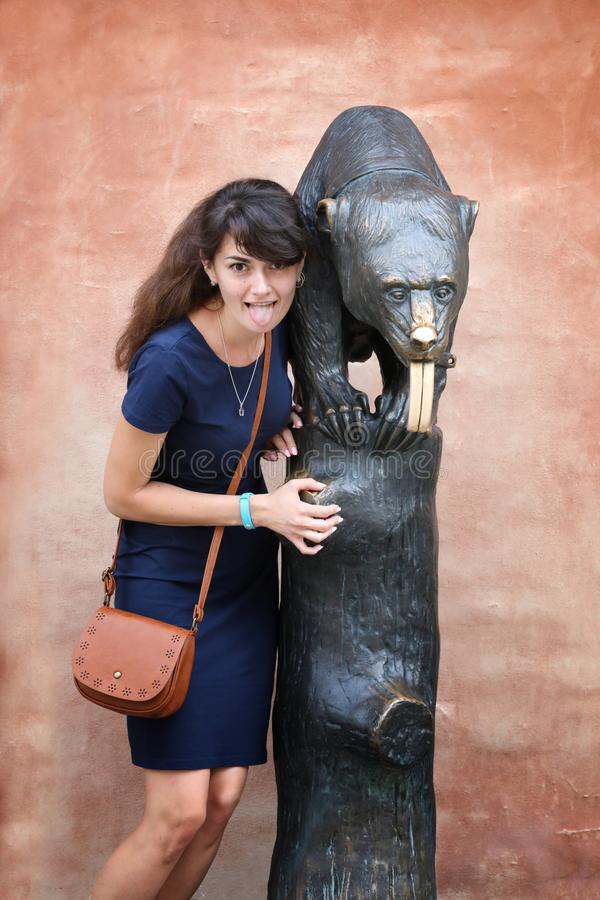 Girl and statue of a bear with a long tongue at the Town Hall in royalty free stock images