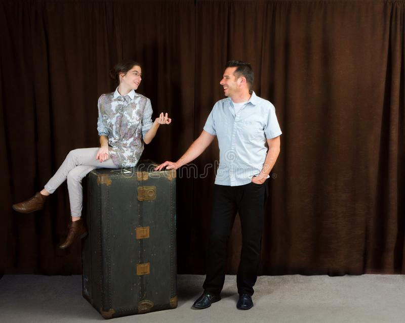 Girl On Steamer Trunk Explains Something To Man Standing Next To royalty free stock images