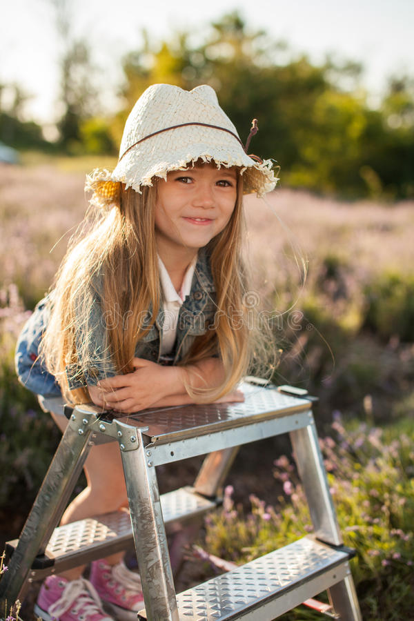 Girl on a stepladder in fairy field of lavender. royalty free stock images