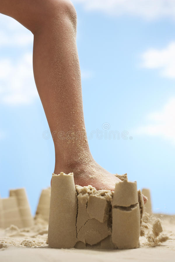 Girl Stepping On Sand Castle royalty free stock photography