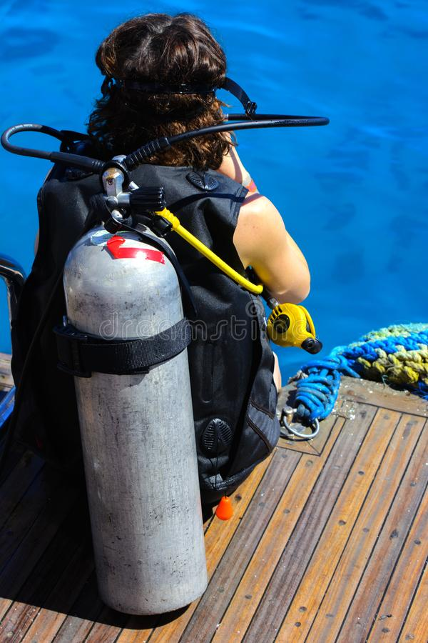 A girl at the stern of a ship in a diving suit prepares to immerse herself in a transparent and turquoise Red Sea stock image