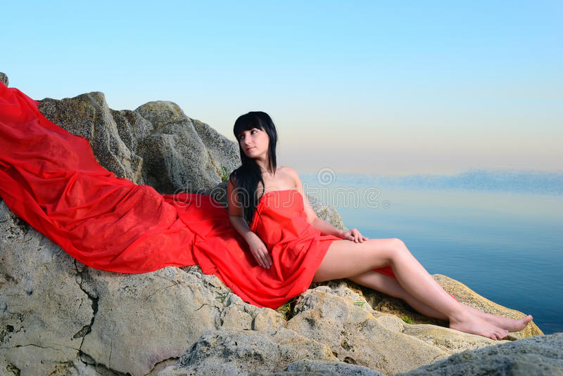 Download The Girl On Stones In A Red Fabric Stock Photo - Image: 25433598