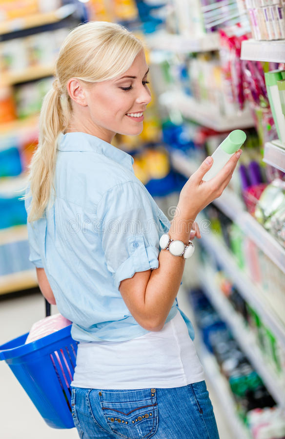 Girl at the store choosing cosmetics royalty free stock photography