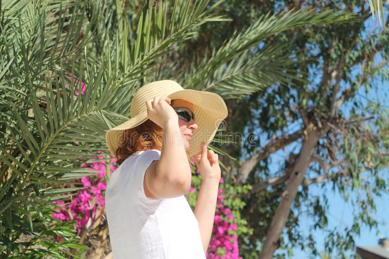 Girl in straw hat in front of palm tree stock photos