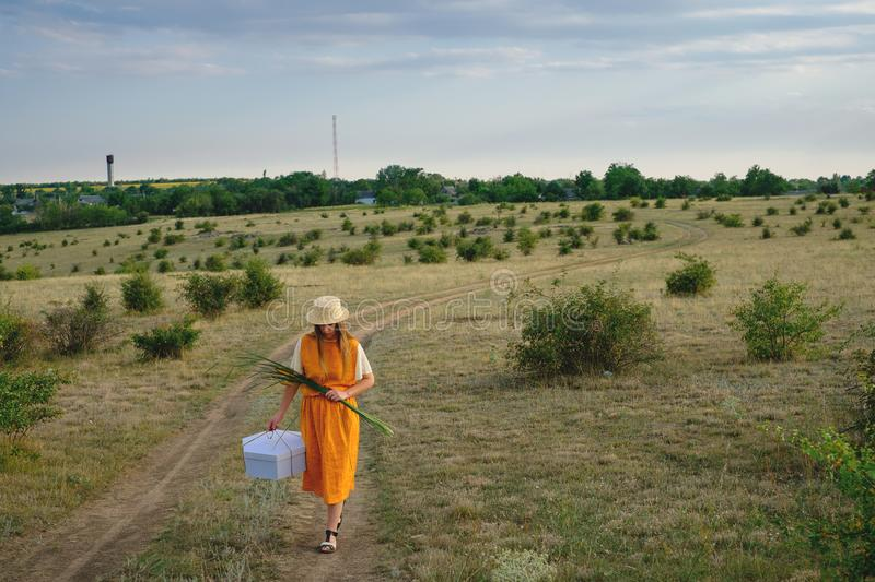 A woman in a straw hat and a gift box walks royalty free stock photography