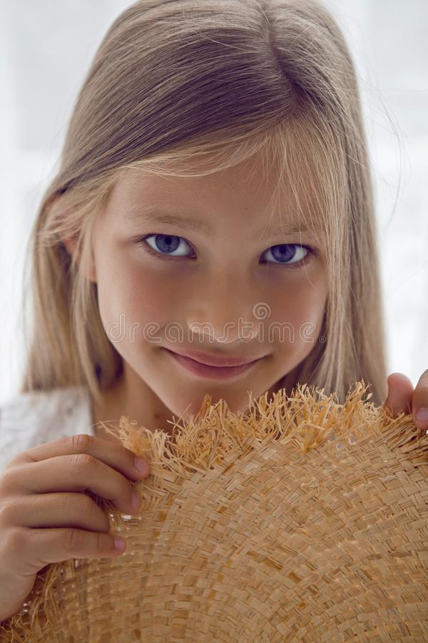 Girl in the straw hat stands at the window stock images