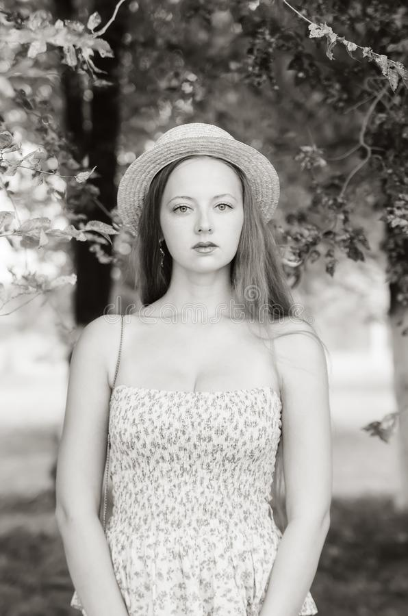 Girl in a straw hat and summer dress posing in a city park stock photos