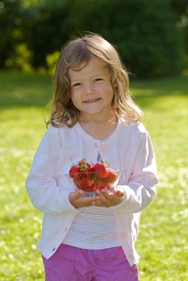Girl with strawberry. Young girld holding a glass bowel with fresh strawberrys stock photo
