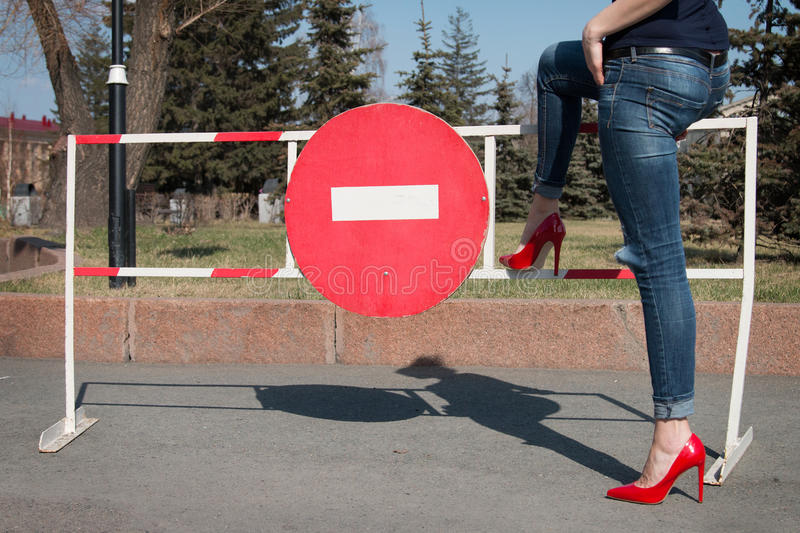 Girl on the street in red patent leather shoes. stock photo
