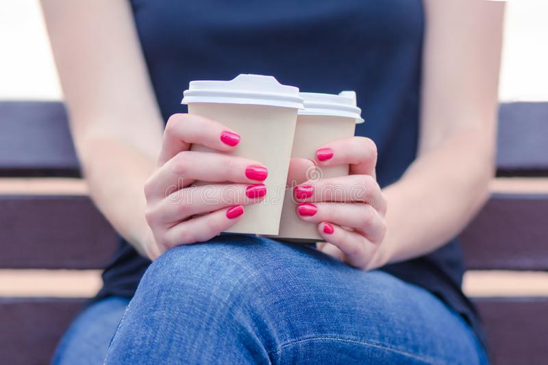 Girl on the street sits on a bench during the day. in hands with red manicure holds 2 disposable cups with tasty aromatic coffee. royalty free stock image