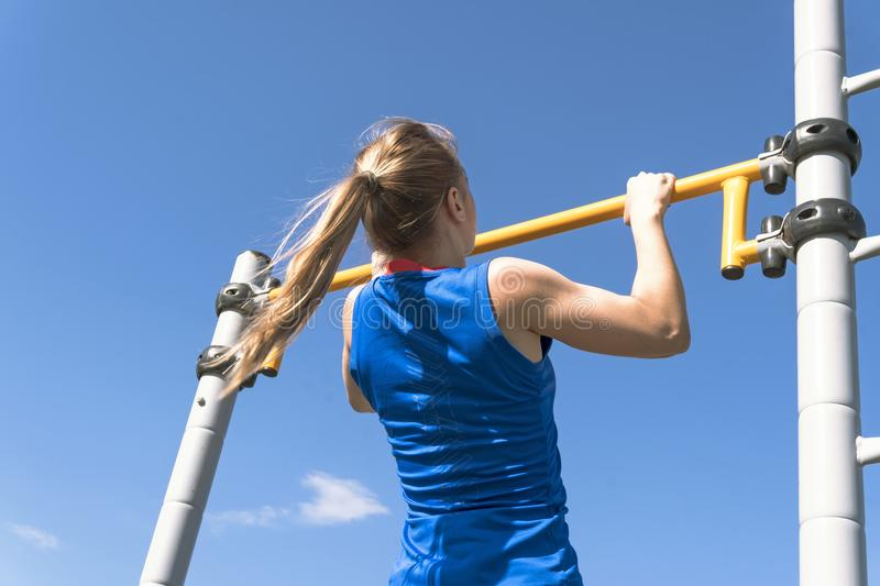 Girl on street workout. She pull-ups herself up on bar on sports ground in park. Photo from the back. Man is unrecognizable.  stock photography