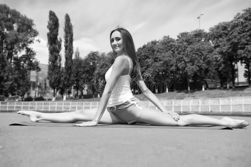 Girl stretching legs after workout. Split is easy for her. Stretching muscles every time training. Coach tips and advice. Woman flexible body practice split on stock image