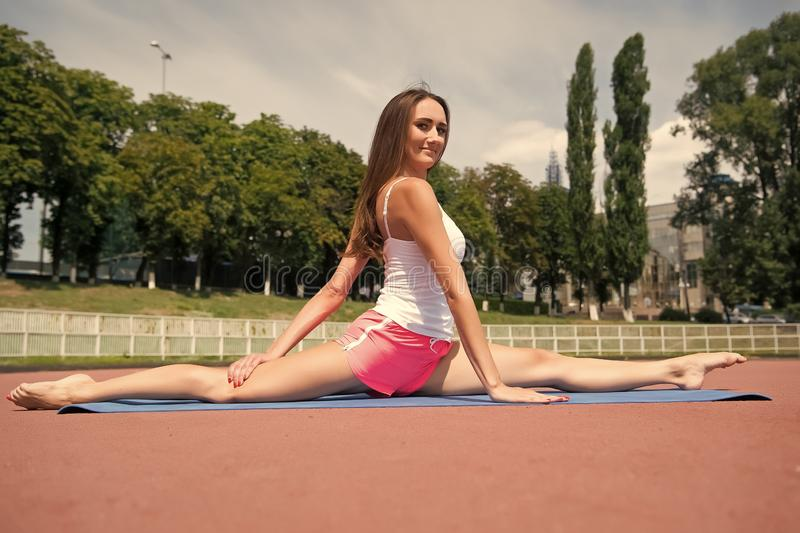 Girl stretching legs after workout. Split is easy for her. Stretching muscles every time training. Coach tips and advice. Woman flexible body practice split on stock images