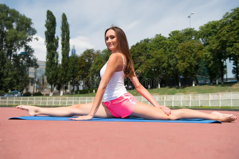 Girl stretching legs after workout. Split is easy for her. Stretching muscles every time training. Coach tips and advice. Woman flexible body practice split on stock photos