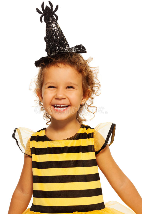 Girl in striped bee costume wearing spider hat. Laughing little girl in costume of a bee and Halloween hat with spider standing isolated royalty free stock photography