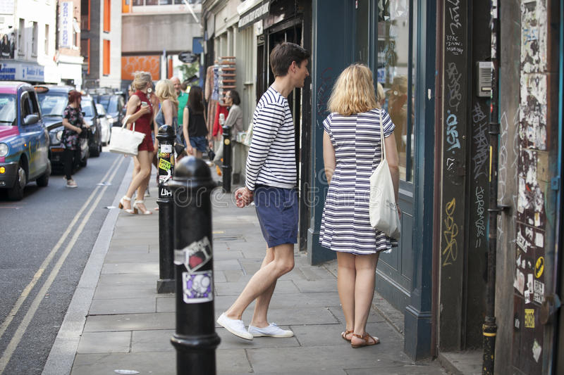 Girl in a striped dress and a boy in a striped T-shirt standing near the store, looking at shop window stock image