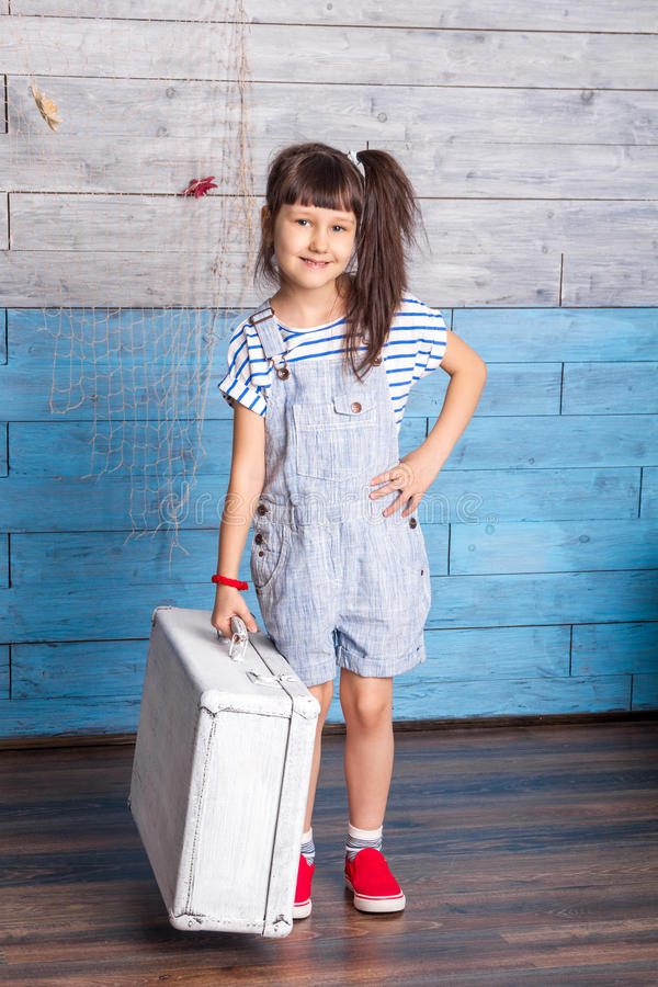 Girl in a striped dress holding suitcase stock image