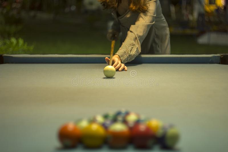 A girl in a striped dress holds a cue over a pool table with blue cloth and blurred billiard balls stock photos